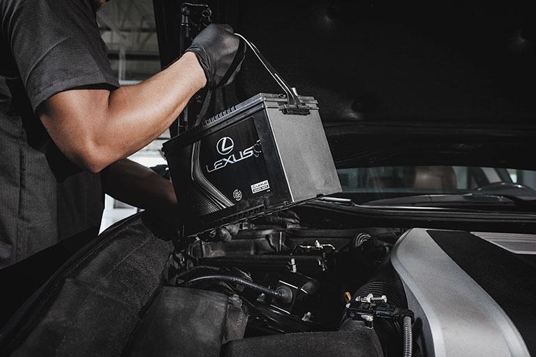 Mécanicien Lexus installant une batterie Premium dans une voiture