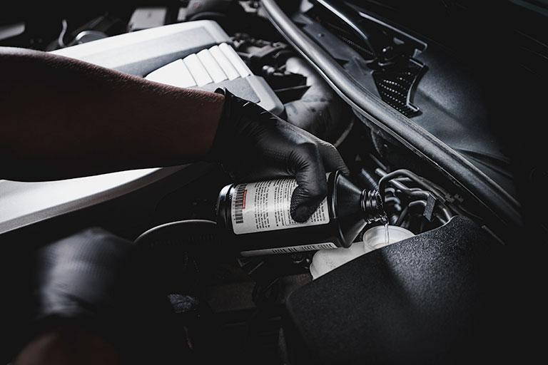 Mécanicien Lexus versant du liquide de refroidissement dans une voiture