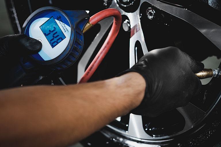 Mécanicien Lexus vérifiant la pression des pneus