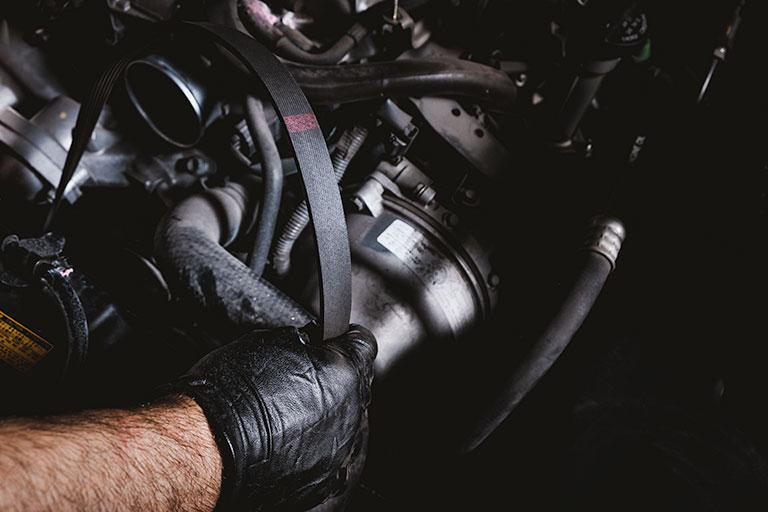 Mécanicien Lexus remplaçant une courroie de distribution dans une voiture