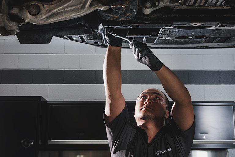 Mécanicien Lexus effectuant une vidange l'huile sous une voiture