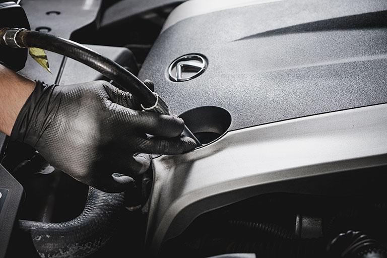 Mécanicien Lexus effectuant une vidange l'huile