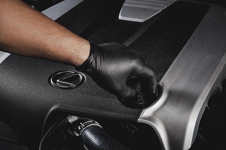 Mécanicien Lexus ouvrant le bouchon d'huile