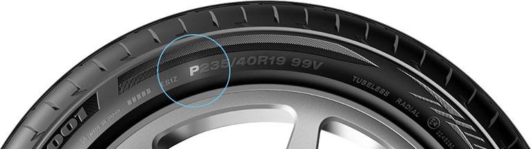 Gros plan sur la lettre « P » indiquant les dimensions P-métrique d'un pneu de voiture de tourisme